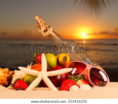 Summer concept with sandy beach, shells and starfish. Sunset background - stock photo