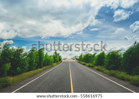 Summer Country Road With Trees Beside Concept , highland road , asphalt road through the green field and clouds on blue sky in summer day