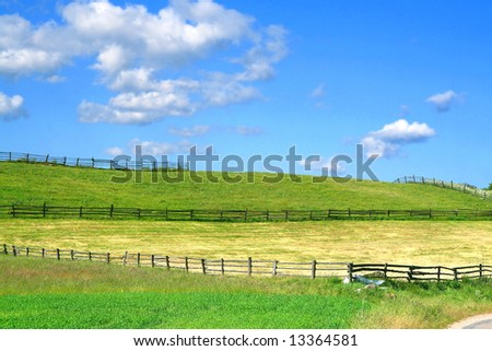 summer country view with fields and wooden fences, focus set in foreground - stock photo