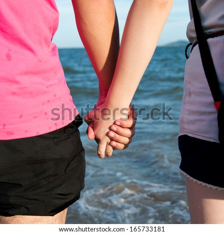 Summer couple holding hands in front of the sea. - stock photo