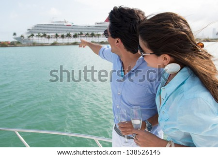 Summer couple on the boat pointing at a cruise - stock photo