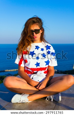 Summer cute portrait of young teen girl having fun and go crazy, wearing trendy top with american flag print,hat, hipster mirrored glasses. Sitting on the terrace with amazing sea view. Joy Sea Sunset - stock photo
