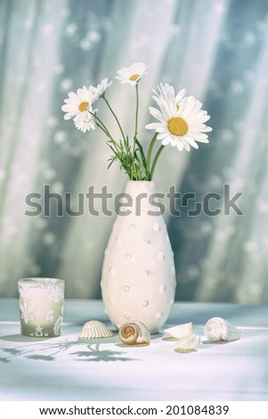 Summer daisies in vase on table - stock photo