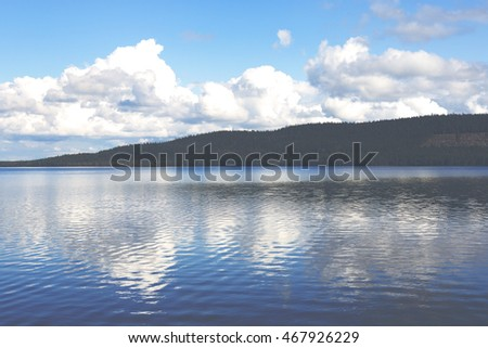 Summer day in Finland. Clouds are reflected from the water. Image taken in Finland.