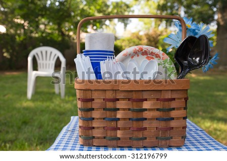 Summer day picnic basket with plastic cutlery and paper plates in outdoor setting - stock photo