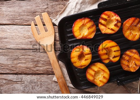 Summer dessert: Cooking Ripe peaches on a grill pan on the table close-up. Horizontal view from above