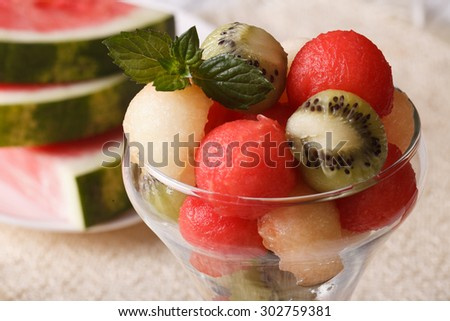 Summer dessert: fruit balls of watermelon, kiwi and melon with mint in a glass closeup. horizontal