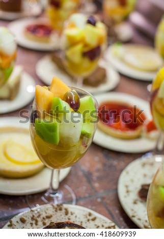 Summer dessert - glass full of fresh fruit pieces, including apples, grapes and orange - stock photo