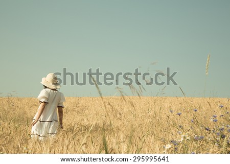 Summer dreams. Girl walking in a field of wheat with blue sky retro background. - stock photo