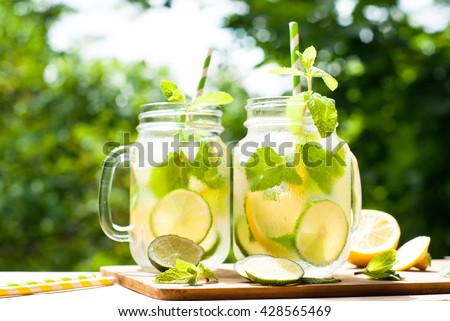 Summer drink lemonade mojito with lime, lemon  and mint in mason jar outdoor. - stock photo