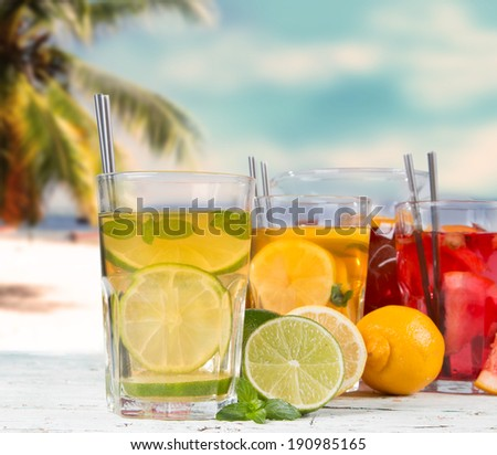 Summer drinks on wooden table. Cocktails with blue sky, tropical beach and fresh fruits. - stock photo