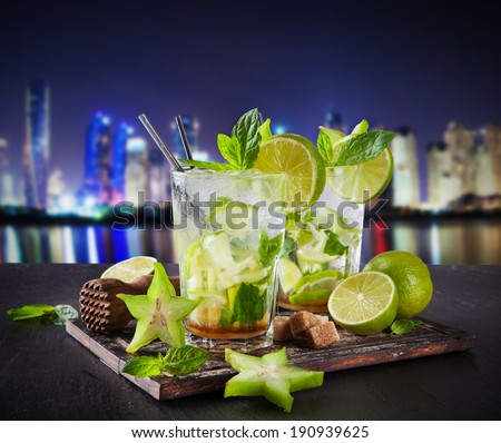 Summer drinks with blur night modern city on background - stock photo