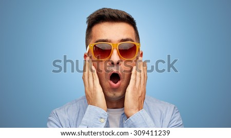 summer, emotions, style and people concept - face of scared or surprised middle aged latin man in shirt and sunglasses over blue background - stock photo