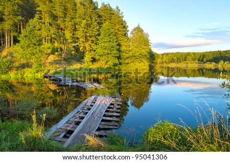 Summer evening. Colorful landscape with a wooden bridge over the river - stock photo