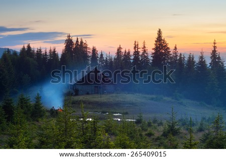 Summer evening. Mountain landscape. Camping in nature. Bonfire near the house - stock photo