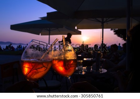 Summer evening orange ice cocktail in a bar by the sea at the sunset, with the colorful sky in the background and the silhouettes of the people - stock photo