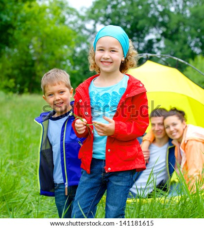 Summer, family camping - lovely sister and brother with parents near camp tent - stock photo