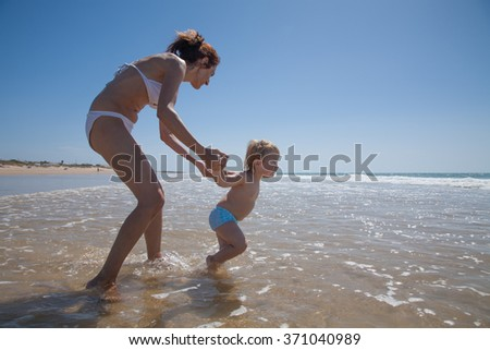 summer family of two years blonde brave baby with blue swimsuit walking and pulling woman mother bikini to ocean at sea shore beach sand in Cadiz Andalusia Spain
