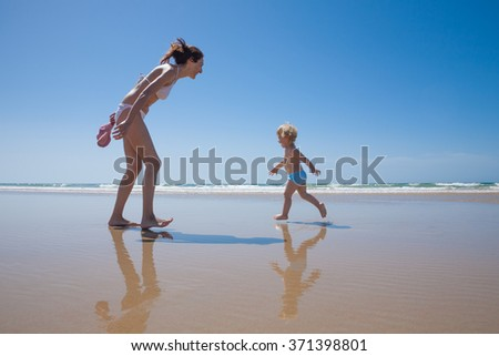 summer family of two years old blonde baby with blue swimsuit running with brunette woman mother in white bikini at sea shore beach sand in Cadiz Andalusia Spain