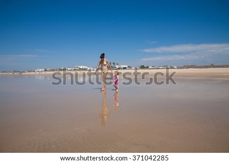 summer family of two years old blonde baby with pink and yellow swimsuit holding hand with brunette woman mother in bikini walking at sea shore beach sand in Cadiz Andalusia Spain - stock photo