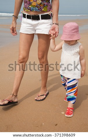 summer family of two years old blonde baby with pink hat white shirt and colorful trousers holding hand with woman mother white jeans shorts walking at beach sand in Cadiz Andalusia Spain - stock photo