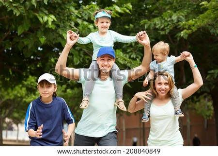 Summer family portrait of parents and three children in the park - stock photo