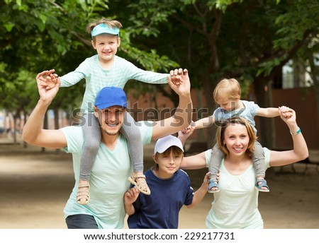 Summer family portrait of parents and three children outside - stock photo