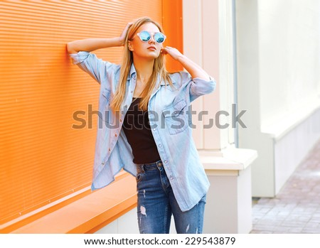 Summer, fashion and people concept - bright stylish pretty woman in sunglasses against colorful wall in city, street fashion - stock photo