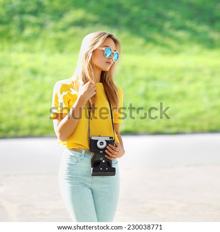 Summer, fashion and people concept - stylish pretty modern girl in sunglasses with retro vintage camera posing in city, street fashion - stock photo