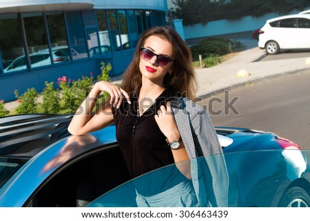 Summer fashion close up portrait of Beautiful young business woman opened her blue sport luxury car at urban modern background.Fashionable young woman posing outside in a city street. Summer Fashion - stock photo