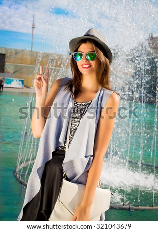 Summer fashion close up portrait of brunette fashionable young woman wearing elegant grey vest, retro hat,hipster sunglasses and elegant white bag.Hipster girl on the shopping at fountain background. - stock photo