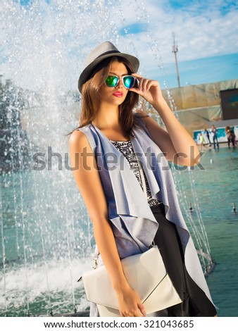 Summer fashion close up portrait of brunette fashionable young woman wearing elegant grey vest, retro hat,hipster sunglasses and elegant white bag.Street fashion,vacation style.Luxury concept. - stock photo