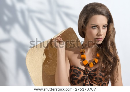 summer fashion  close-up shoot  of sexy brunette woman with long hair, stylish bikini and necklace. taking straw hat in the hand  - stock photo