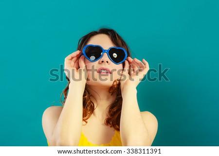 Summer fashion eyes protection concept. Closeup girl long curly hair in blue heart shaped sunglasses