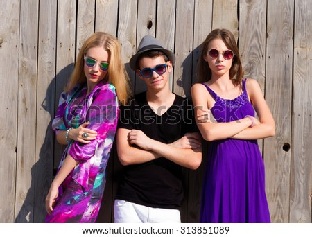 Summer fashion image of beautiful thee friends ,man and two woman around he at wooden wall background.The best friends.Three young teenage students standing together,wearing dresses,ready for party - stock photo