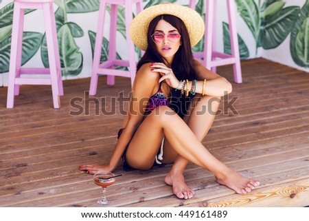 Summer fashion image of  young  woman in sexy beach bikini with tasty cocktail  sitting on wood floor in stylish  cafe .  Wearing boho accessories, straw hat, pink sunglasses.  - stock photo