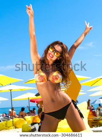 Summer fashion photo of beautiful tanned woman with brunette hair in sexy bikini relaxing at luxury beach resort on yellow beach chair. Summer close up of slim sexy woman going crazy on vacation. - stock photo
