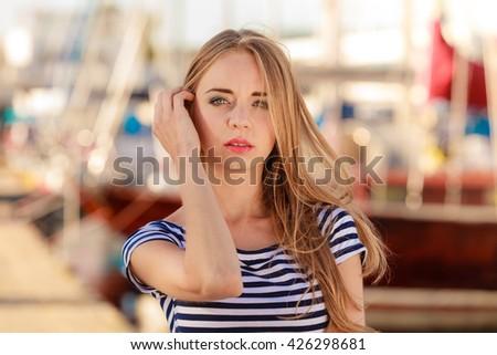 Summer fashion. Portrait girl enjoying summer breeze at sunset in marina - stock photo