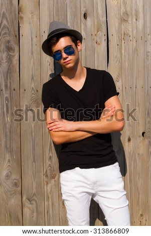 Summer fashion Portrait of a man looking at the camera. He is wearing a hat,casual outfit and sunglasses.Handsome young man in an urban lifestyle fashion pose leaning against an wooden wall. - stock photo