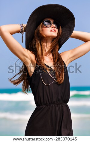Summer fashion portrait of beautiful woman enjoy windy sunny day near ocean, vacation style. Young stylish girl wearing black romper vintage hat and big sunglasses, bright colors, freedom, happiness . - stock photo
