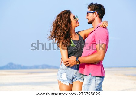 Summer fashion portrait of young pretty stylish hipsters couple in love hugs and posing at amazing island beach, having fun alone, wearing bright casual clothes and sunglasses. - stock photo