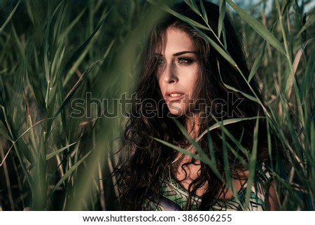 summer fashion young woman portrait in reed in river water at sunset - stock photo