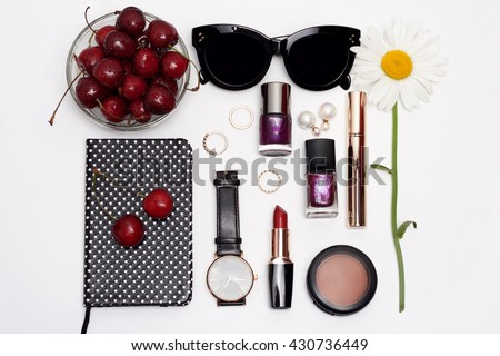 Summer female set of fashion accessories on white background. Stylish sunglasses, nail polish, watch, notebook, lipstick and cherry. Overhead of essentials for young woman. - stock photo
