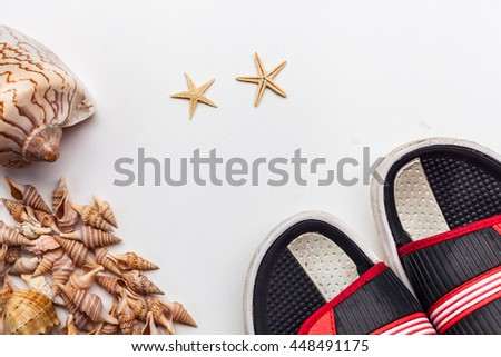 Summer flat lay of beach set items - sea small and large shells, stars and flip flops on clean white background. Top view for tourism, beach holiday and travel image - stock photo