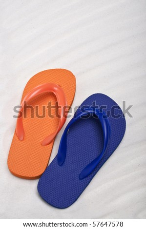 Summer Flip Flop Sandals on a Sand Background.