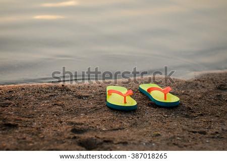 Summer flip flops on the sunset beach - stock photo