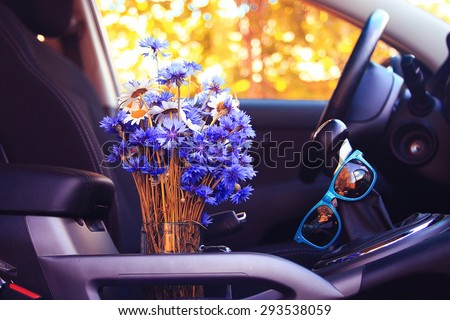 Summer flowers in the car - stock photo