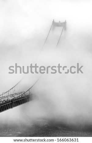 Summer fog does it's best to consume the south tower of the Golden Gate Bridge. - stock photo