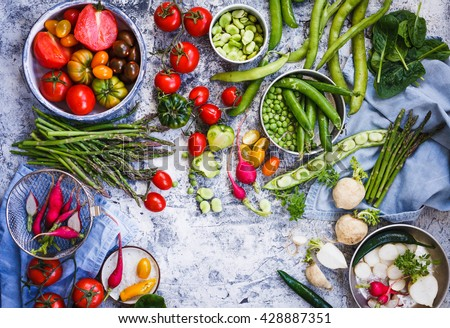 Summer food table with variety vegetables tomatoes, white and red radish, green peas and beans, pepper, spinach leaves, asparagus. Top view. - stock photo