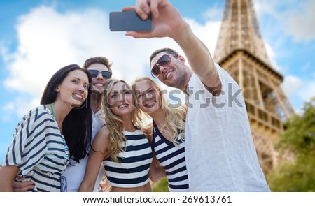 summer, france, tourism, technology and people concept - group of smiling friends taking selfie with smartphone over eiffel tower in paris background - stock photo